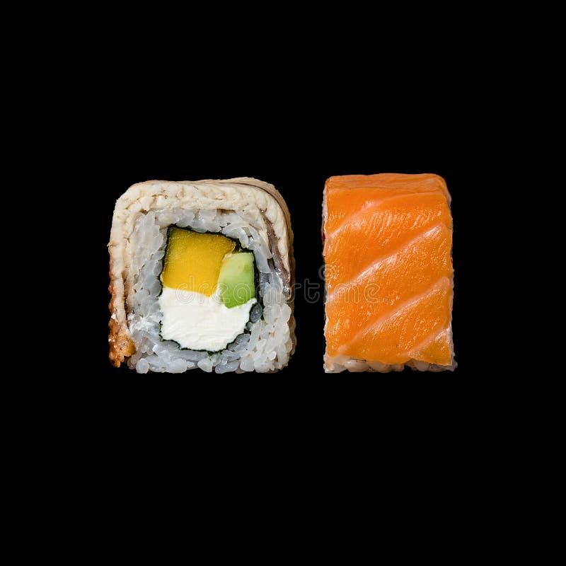寿司 卷用芒果、鲕梨,奶油奶酪和三文鱼,隔绝在黑背景中 图库摄影