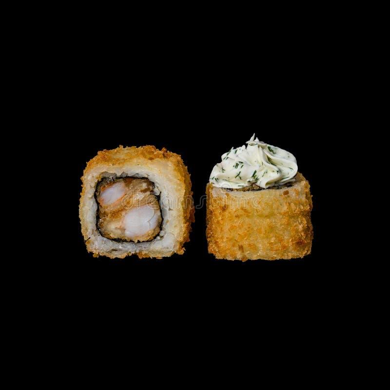寿司 被烘烤的卷用天麸罗虾、奶油奶酪和草本,隔绝在黑背景中 免版税库存图片