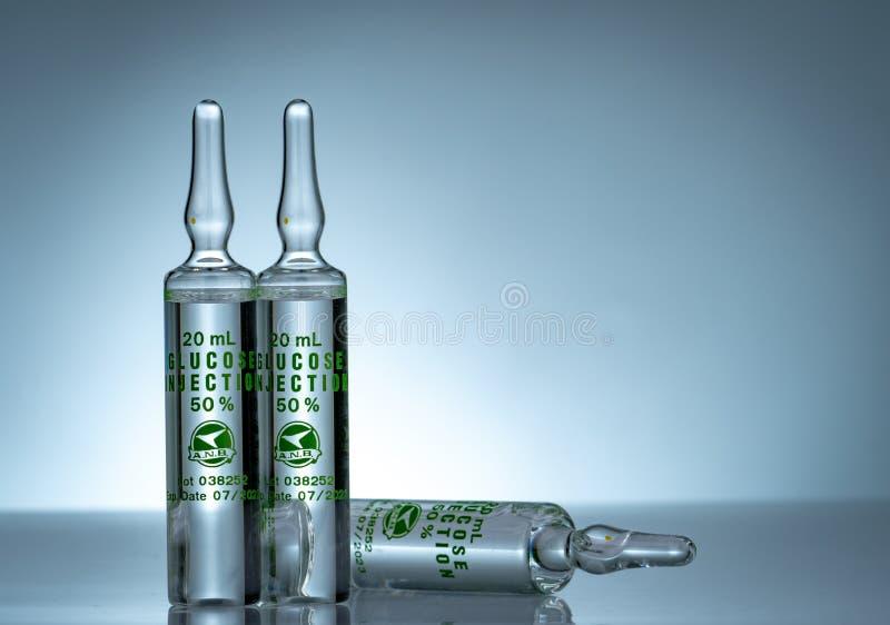 射入的葡萄糖50%在20 ml一次用量的针剂 葡萄糖三玻璃一次用量的针剂射入的在梯度背景 免版税库存照片