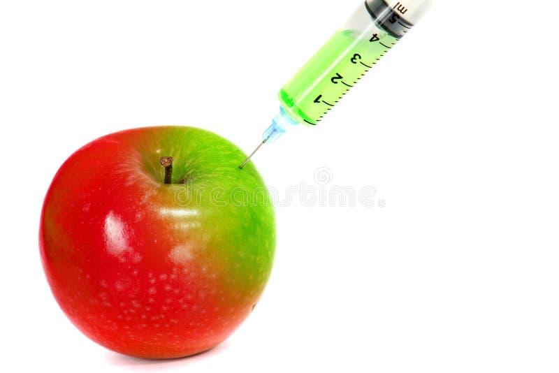 射入绿色到与注射器的红色新鲜的湿苹果里在白色背景为更新能量,疗法或刷新或者促进能量 免版税图库摄影
