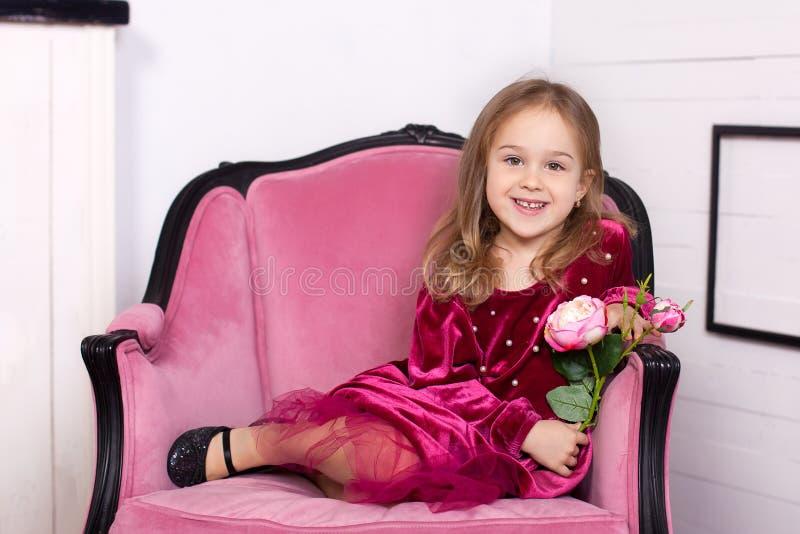 射击一件礼服的一美丽的女孩有一朵玫瑰的在她的看与迷人的微笑的手上照相机坐胳膊 免版税库存图片
