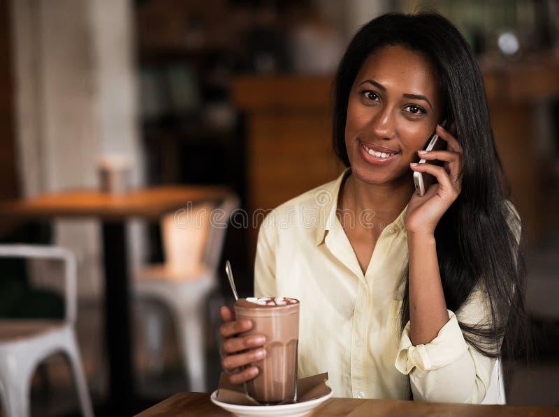 射击一美丽的愉快的非洲妇女微笑的谈话在她的s 免版税库存图片