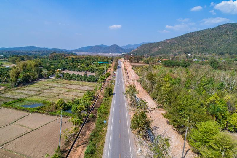 射击从寄生虫的泰国农村路方式去与此外领域和谷的山 在泰国北部 免版税库存照片