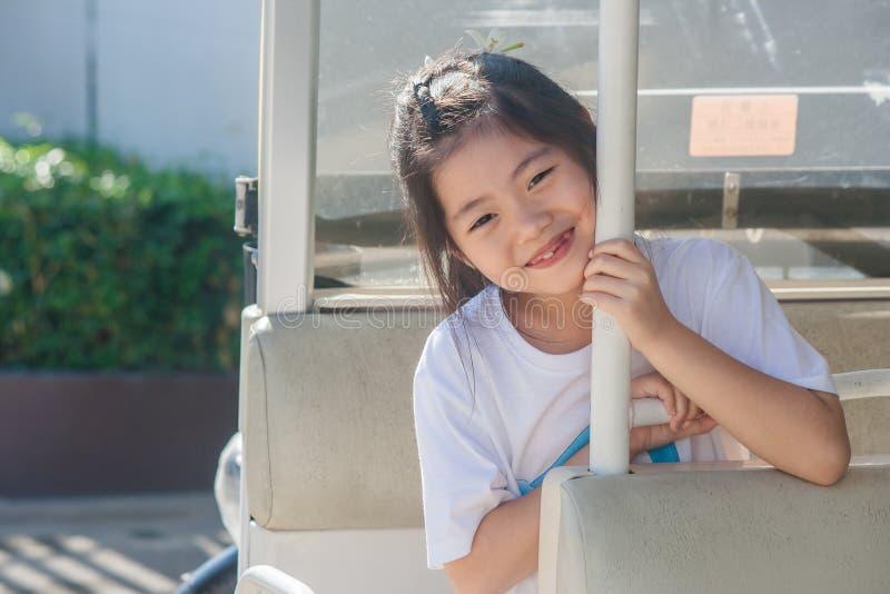 射击在高尔夫球汽车和微笑的亚洲矮小的逗人喜爱的女孩选址 库存照片