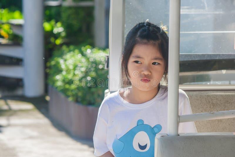 射击在goft汽车的亚洲矮小的逗人喜爱的女孩选址和认为某事 免版税库存照片