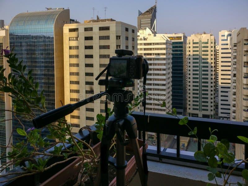 射击日落的时间间隔在一个阳台上在城市-照相机和三脚架 免版税图库摄影