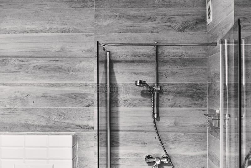 射击有淋浴喷头的一个时髦的黑白卫生间 库存照片