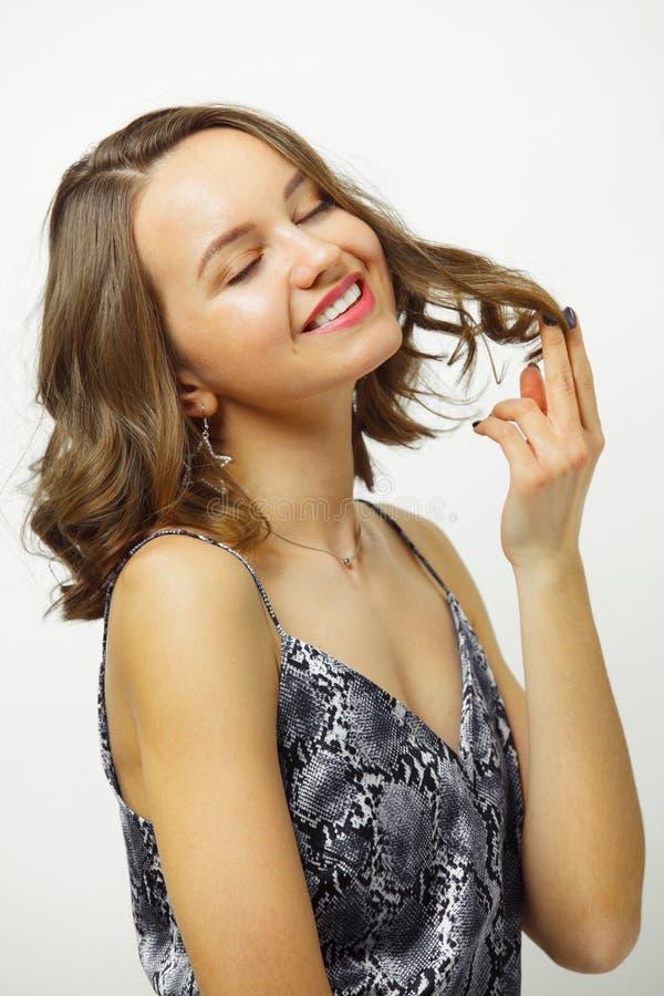射击有短的理发的微笑的妇女,保持头发满意对舒适的发型,享受变动,有恳切 免版税库存照片
