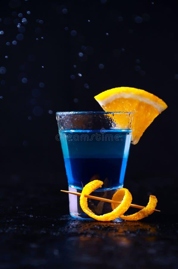射击用白色兰姆酒、酒蓝色库拉索岛和橙色切片 在黑暗的背景的酒精层数鸡尾酒 库存图片
