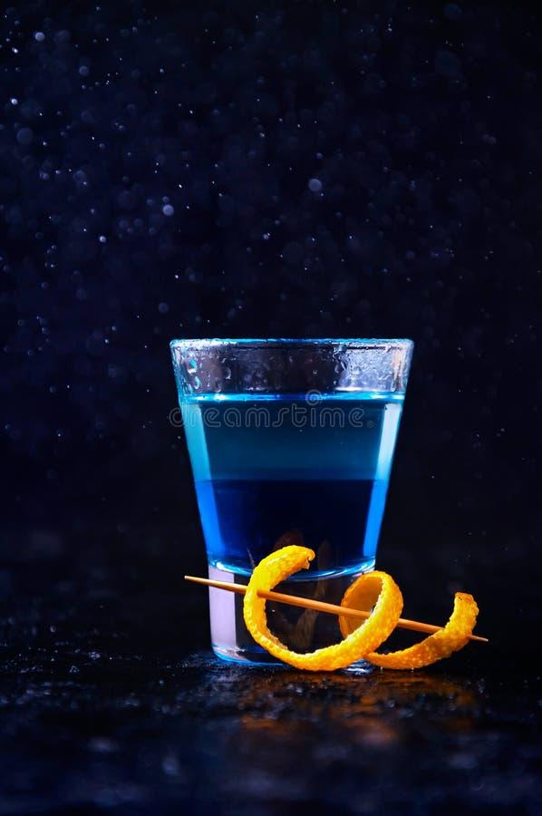 射击用白色兰姆酒和酒蓝色库拉索岛和橙皮 在黑暗的背景的酒精层数鸡尾酒 免版税库存图片