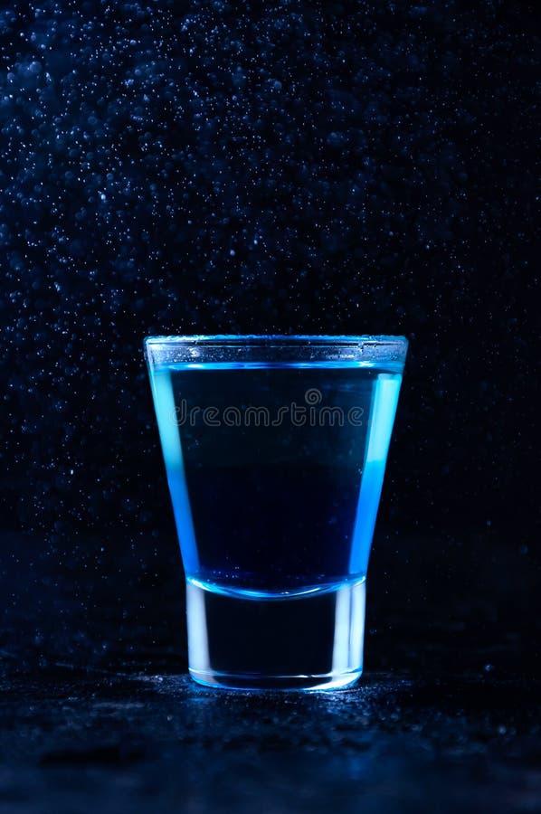 射击用白色兰姆酒和酒蓝色库拉索岛 在黑暗的背景的酒精层数鸡尾酒 免版税库存照片