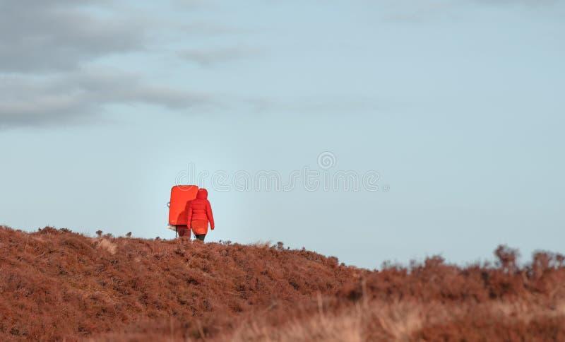 射击的两个徒步旅行者在一次冒险通过草原 免版税库存图片