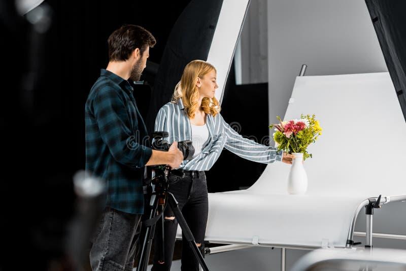 射击美丽的花的专业年轻摄影师 免版税库存照片