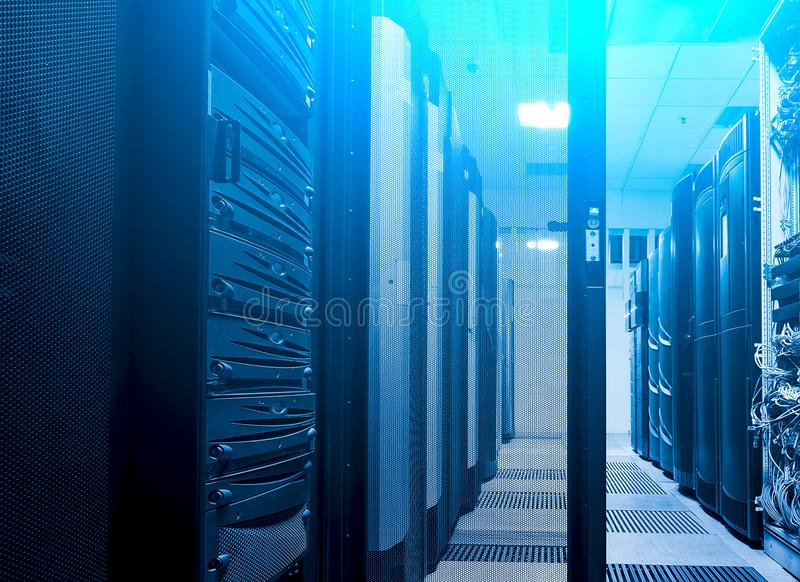 射击走廊在大数据黑暗的服务器室用明亮的蓝色设备 充分机架服务器和巨型计算机 免版税库存图片