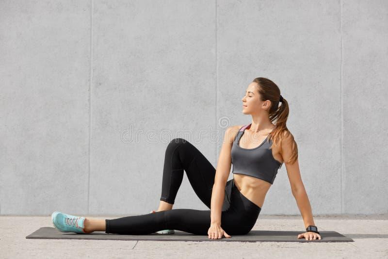 射击轻松的喜悦的妇女休息在心脏训练以后,尝试治疗osteochondrosis,穿戴了随便,在p以后捉住呼吸 库存照片