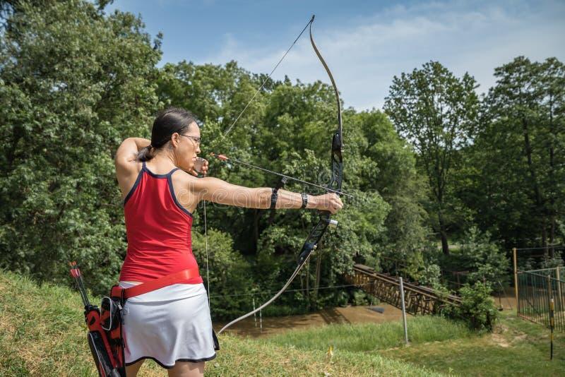 射箭作为体育学科奔跑在大厅里和在自然 最佳的射击的竞争一个箭头到目标里 库存照片