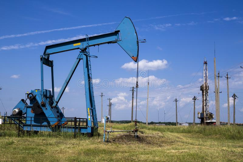 射线脉动单元是家庭作业,日落在油田 石油的油泵抽油装置能量工业机器 脉动单元 图库摄影