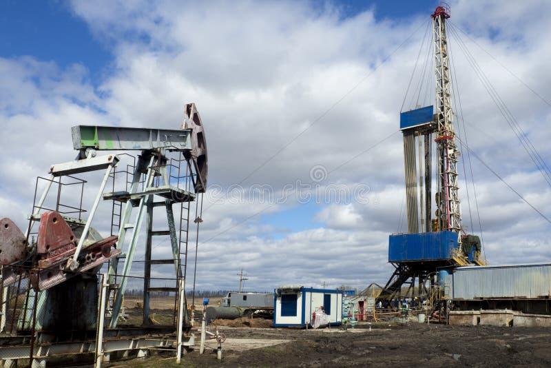 射线脉动单元是家庭作业,日落在油田 石油的油泵抽油装置能量工业机器 脉动单元 免版税图库摄影