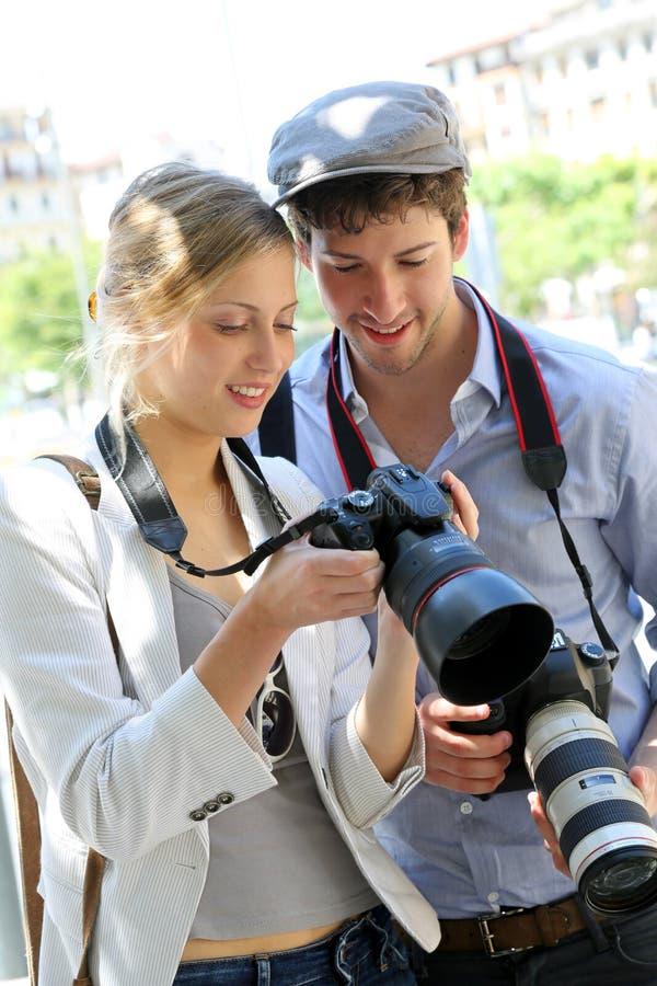 射击在镇里的摄影师夫妇  免版税库存图片
