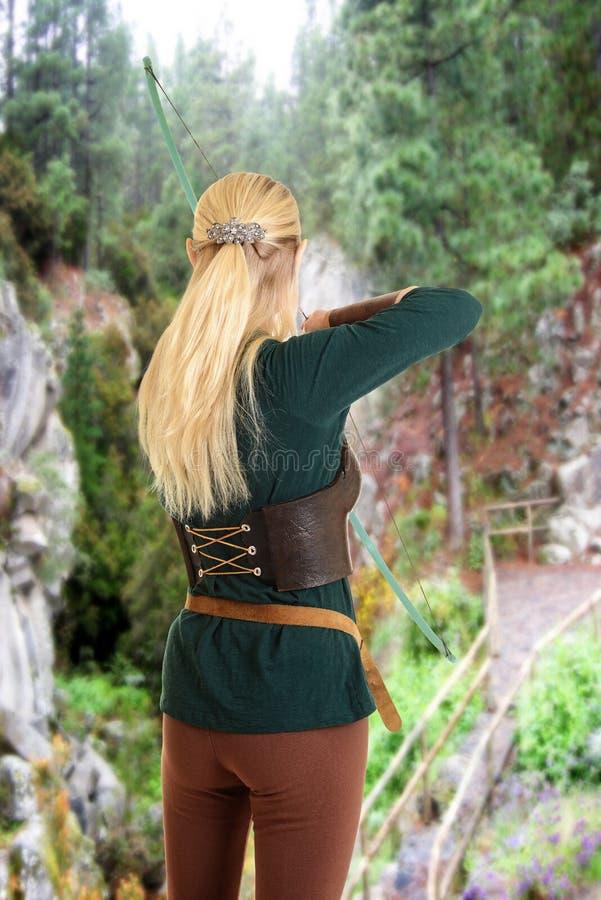 射击弓箭的女性矮子 免版税库存照片