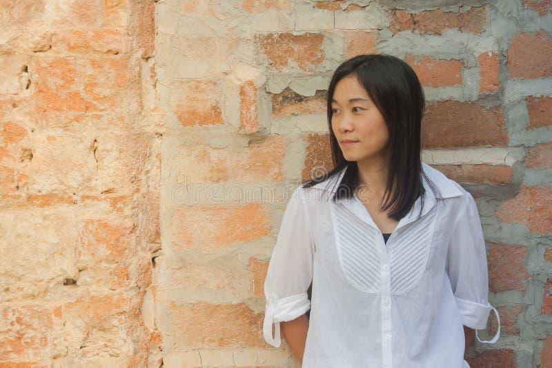 射击照片亚洲妇女画象穿戴白色衬衣和看斜向一边有红砖背景 图库摄影