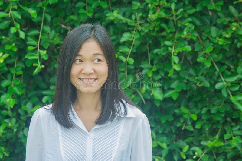 射击照片亚洲妇女画象穿戴白色衬衣,微笑和看斜向一边有绿色树背景 库存照片