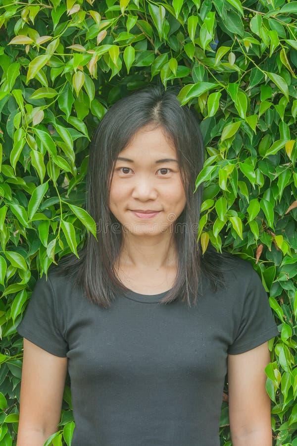 射击照片亚洲妇女画象穿戴黑色T恤杉和微笑有绿色树背景 免版税库存照片