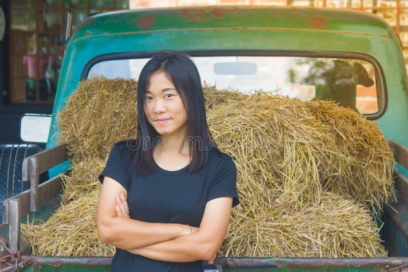 射击照片亚洲妇女画象穿戴黑色T恤杉和横渡有秸杆的一条` s胳膊在葡萄酒汽车背景 库存图片