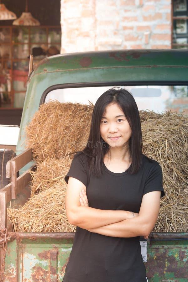射击照片亚洲妇女画象穿戴黑色T恤杉和横渡有秸杆的一条` s胳膊在葡萄酒汽车背景 免版税库存图片
