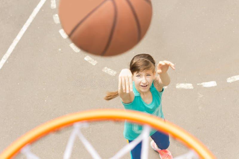射击篮球的可爱的女孩 免版税库存图片