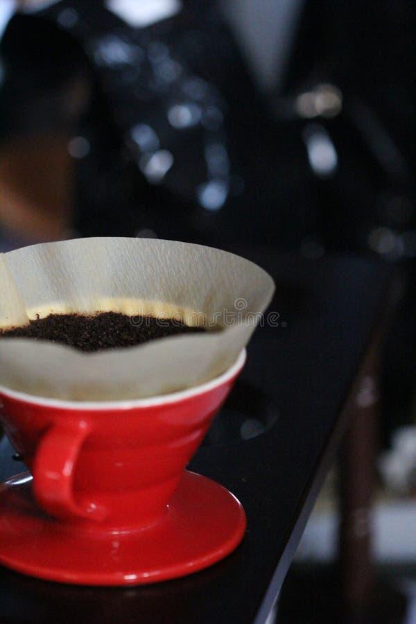 将酿造与一个红色杯子的咖啡粉末 库存照片