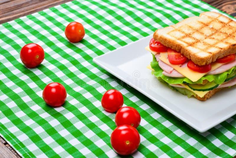 将面包蕃茄、莴苣和黄色乳酪夹在中间 免版税库存照片