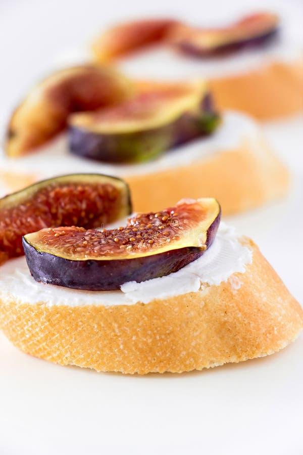 将Bruschetta夹在中间用无花果和山羊乳干酪在白色背景 库存照片