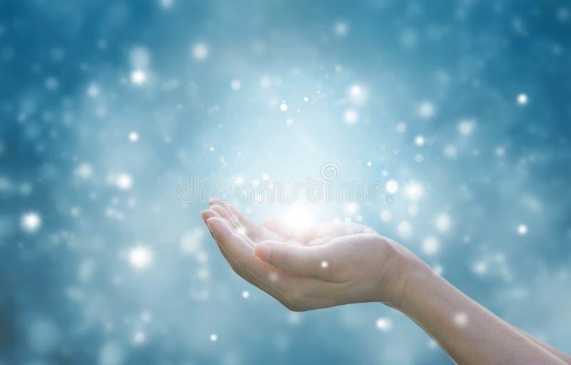 尊敬和祈祷在蓝色微粒的妇女的手 免版税库存图片