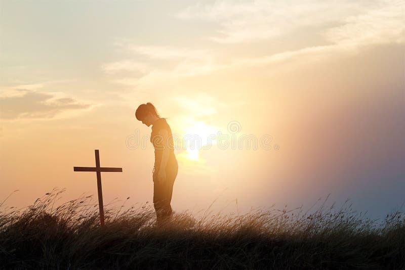 尊敬在日落背景的领域的十字架的妇女 图库摄影