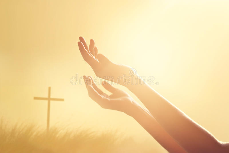 尊敬并且祈祷在十字架和自然日落背景 图库摄影