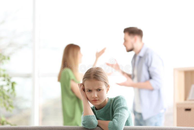 小不快乐的女孩坐沙发,当父母时 免版税库存图片