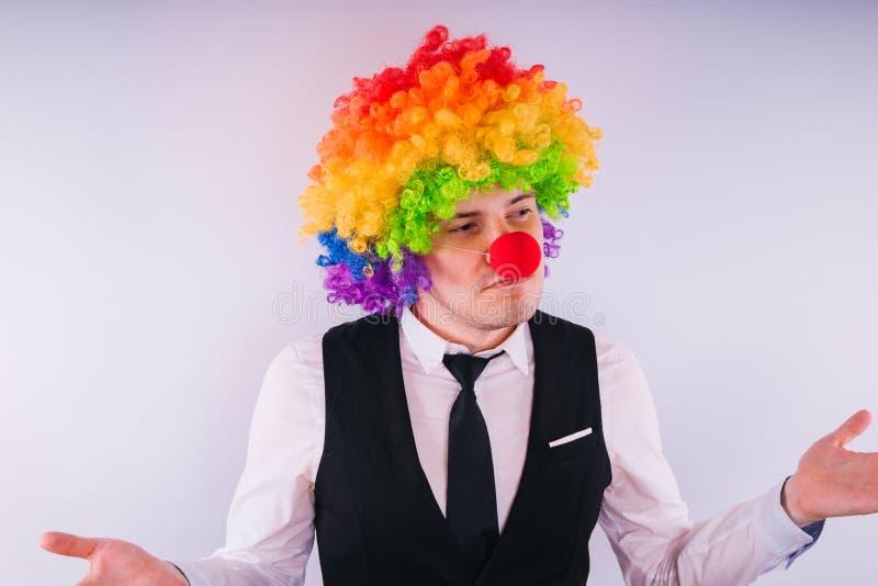 小丑假发的,小丑概念办公室工作者在工作 与在白色隔绝的小丑假发的商人 库存图片