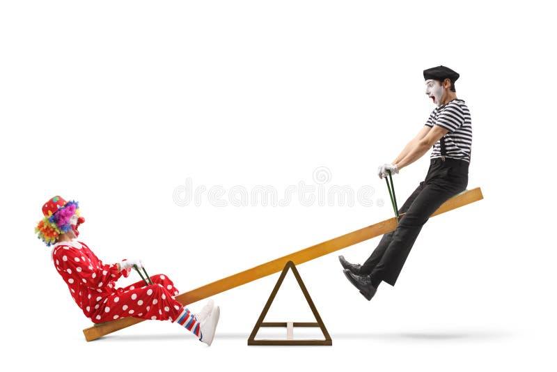 小丑和使用在跷跷板的笑剧 图库摄影