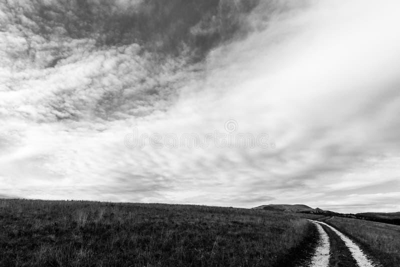 小乡下公路在大天空和白色云彩下 库存照片