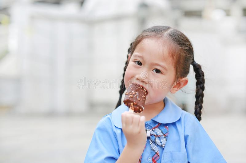小亚裔儿童女孩画象校服的喜欢吃鲜美巧克力香草冰淇淋 免版税库存图片