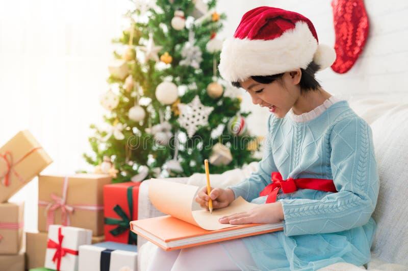 小亚裔儿童女孩给圣诞老人写信 免版税库存图片