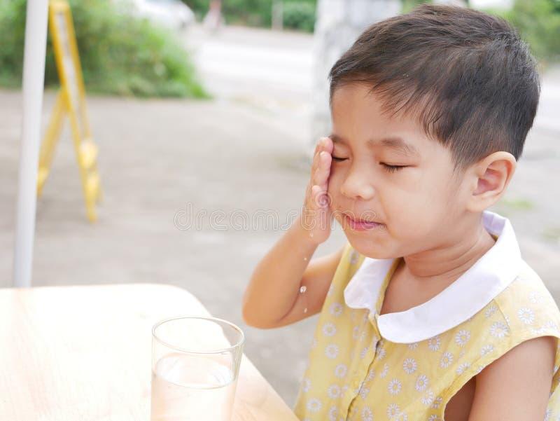 小亚裔女婴喜欢应用在她的面孔的刷新的饮用水 库存照片