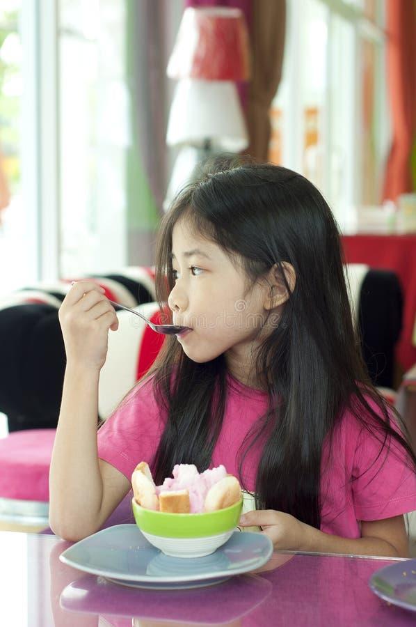小亚裔女孩享用冰霜点心。 免版税图库摄影