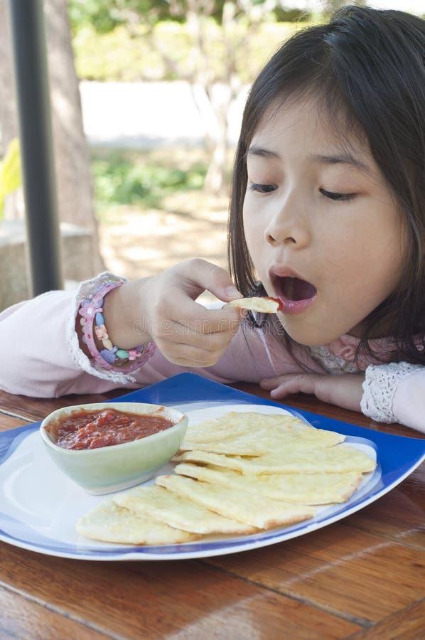 小亚裔女孩享用大蒜乳酪面包。 免版税库存照片