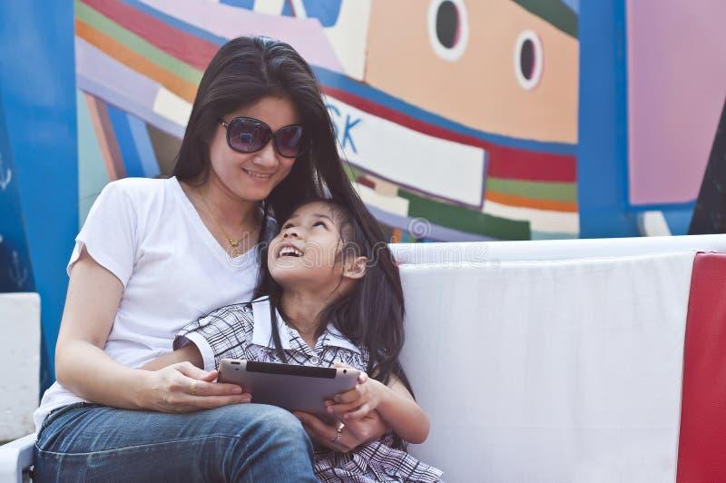 小亚裔女孩和妈妈享用片剂个人计算机。 免版税库存图片