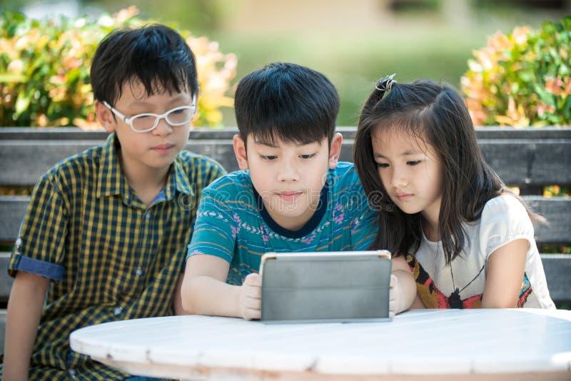小亚裔女孩和男孩坐长的木椅子使用数字 图库摄影