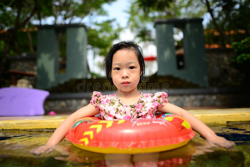 小亚裔女孩在水池游泳  免版税库存照片