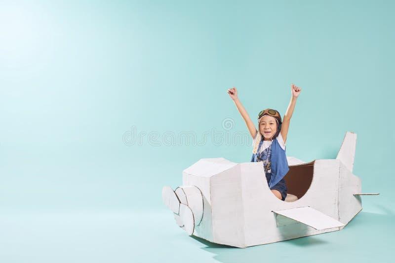 小亚裔女孩是在一架手工制造纸板纸飞机上的愉快的开会 免版税库存照片