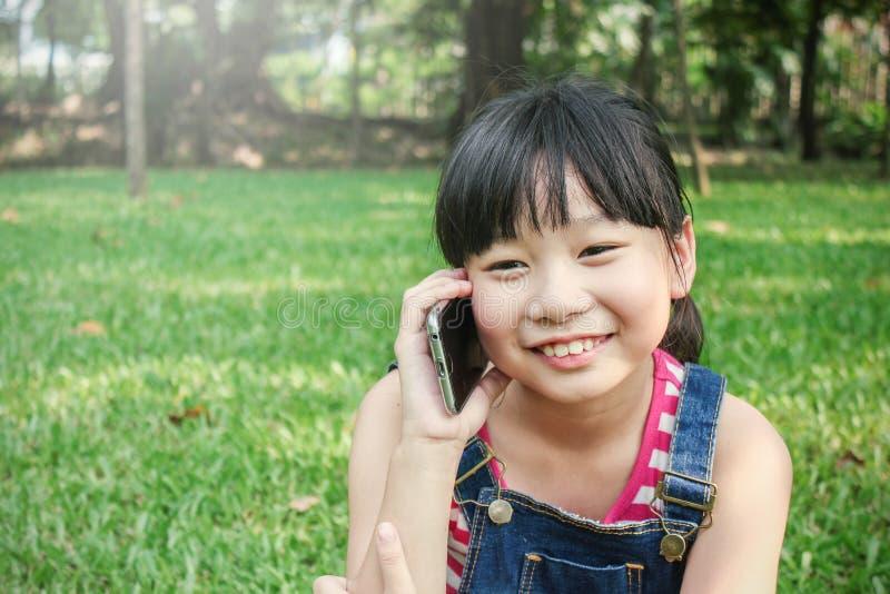小亚裔女孩谈话在手机 免版税库存照片